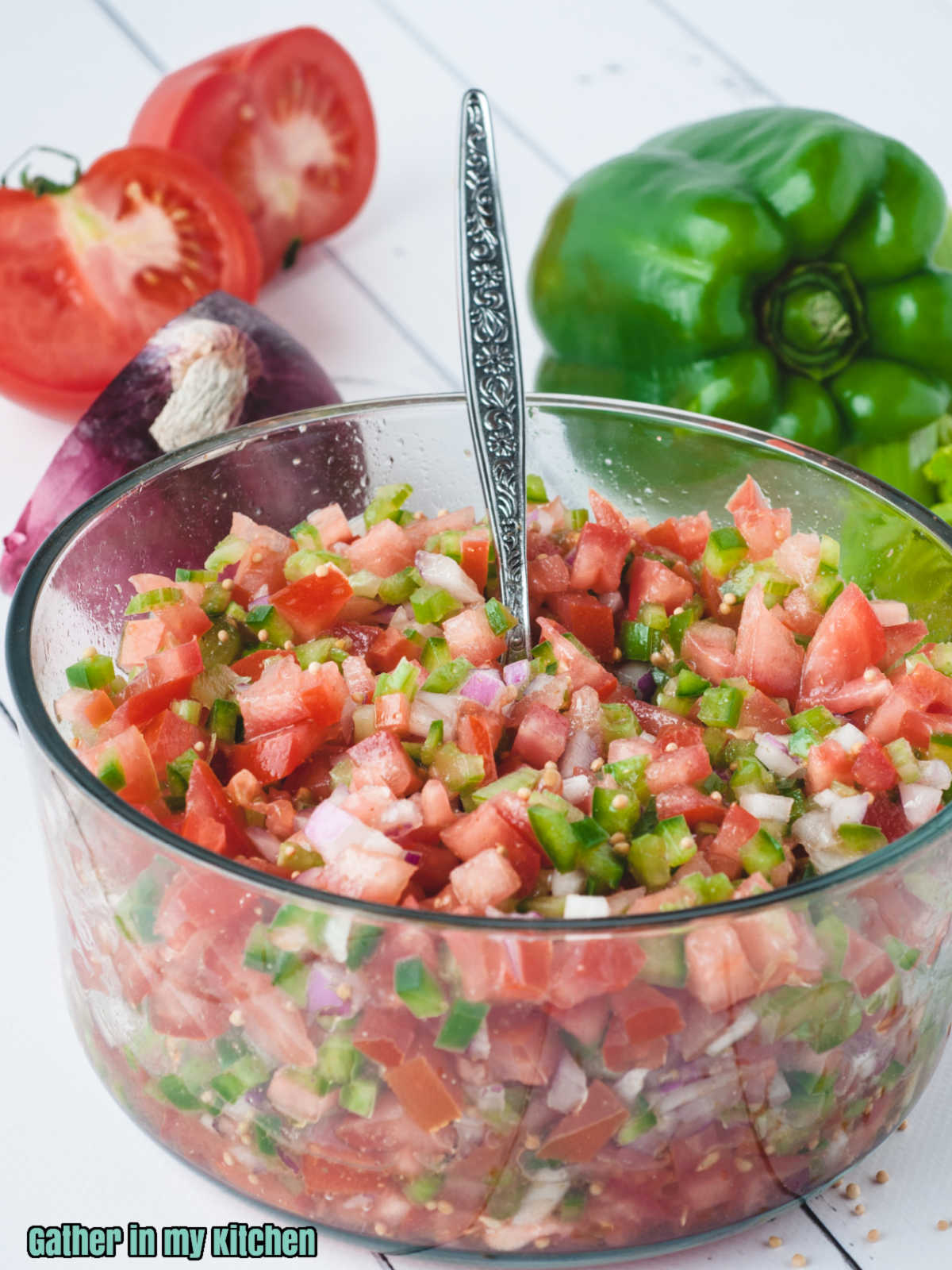 clear bowl with Pico de Gallo and a spoon in it.  Half of a tomato and a full green bell pepper in the background