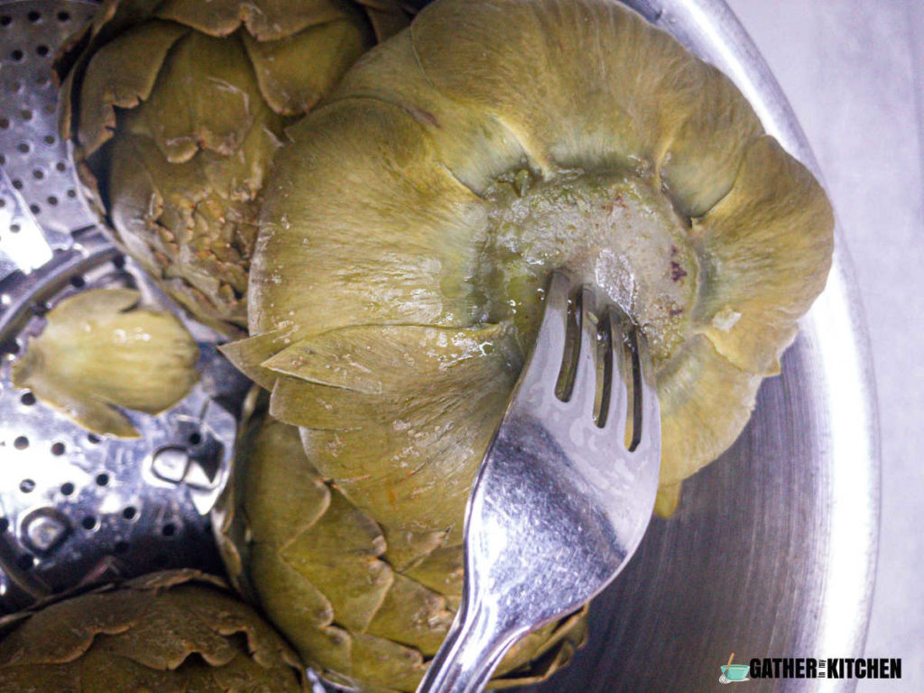 Cooked artichoke flipped over with a fork stuck in the base of it.