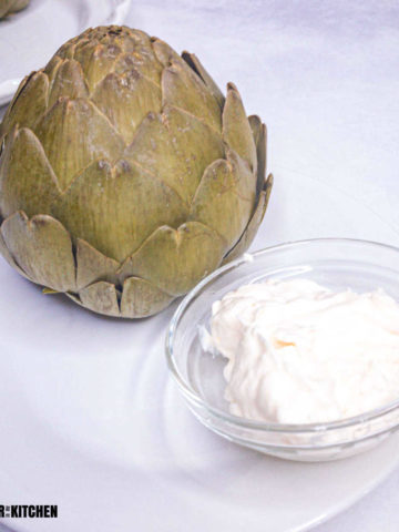 cooked artichoke on plate with small bowl of mayo for dipping.