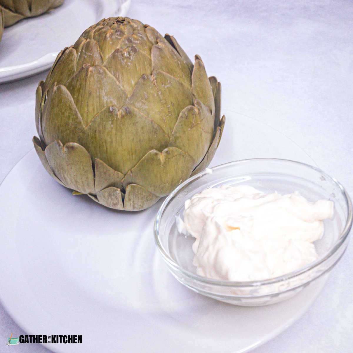 Large artichoke on a plate with a small dish of mayonnaise for dipping.