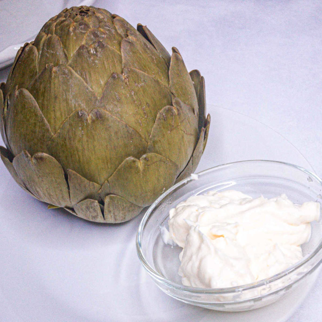 Cooked artichoke on a white plate with a small bowl of mayonnaise dip.