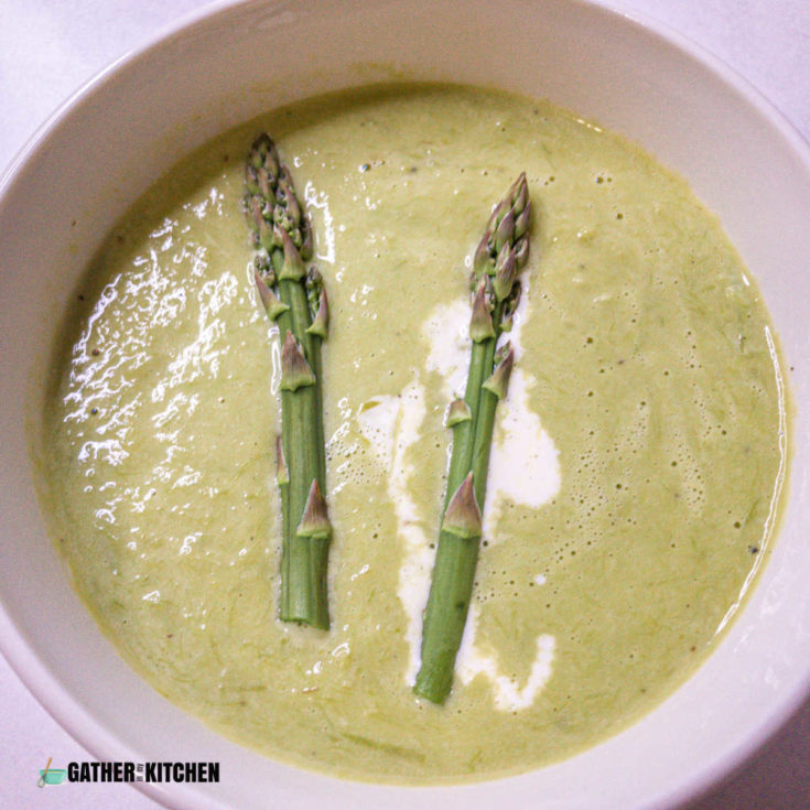 top down view of a bowl of creamy asparagus soup with a drizzle of cream in it as well as two tips of asparagus stalks.