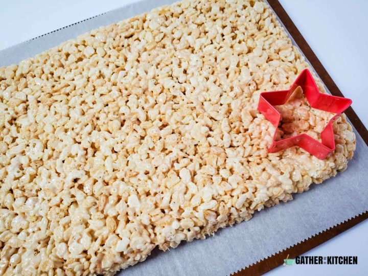 Rice Krispies on parchment paper with a star cookie cutter on top.