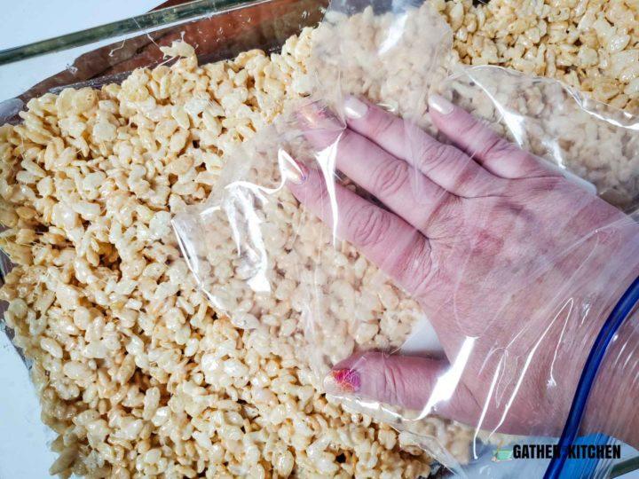 Plastic bag over hand patting down Rice Krispy mix.