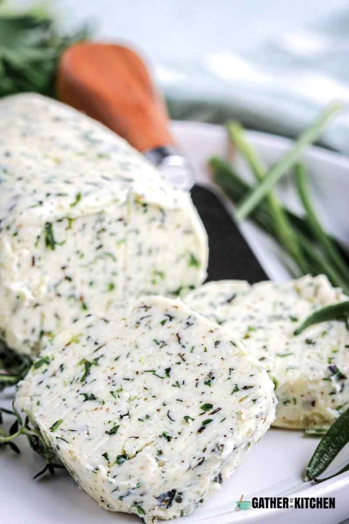 Cutting board with herbs, butter rolled up in parchment paper.