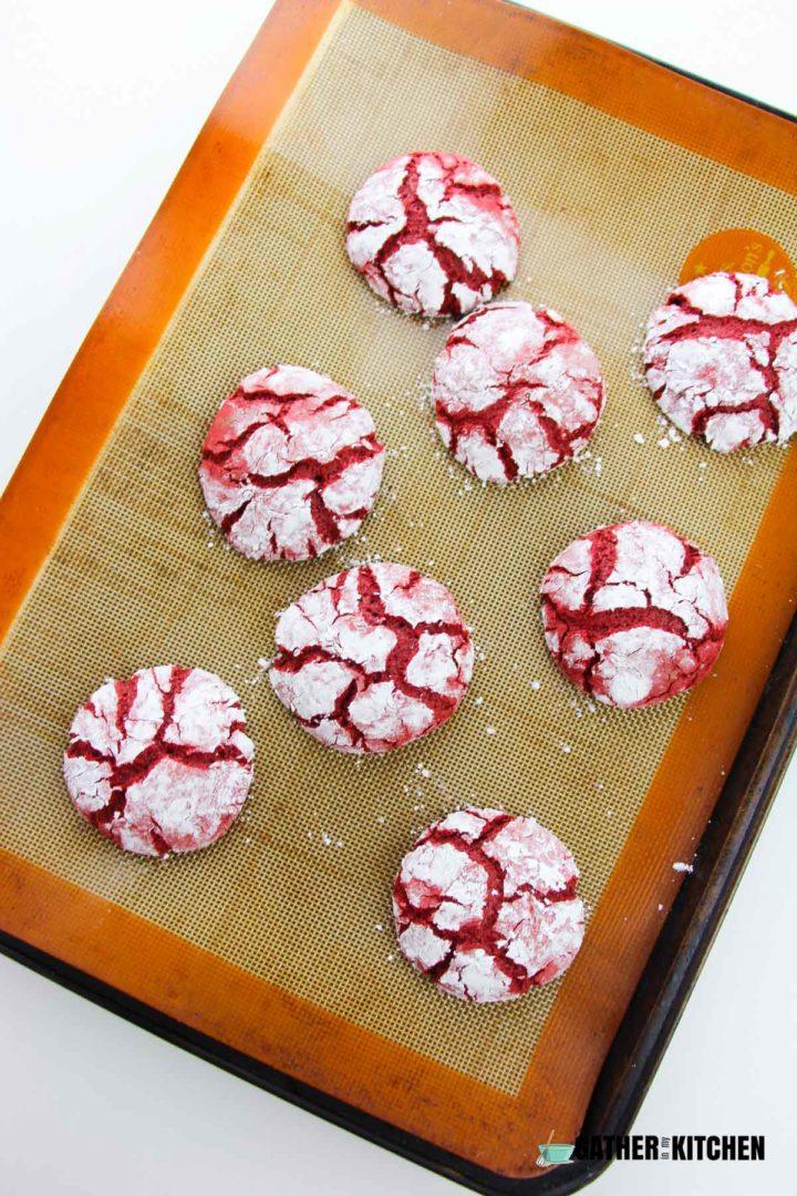 Red Velvet Crinkle Cookies cooked on cookie sheet.