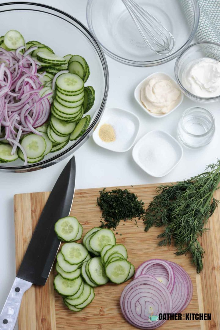 Cut cucumbers and red onion on cutting board.