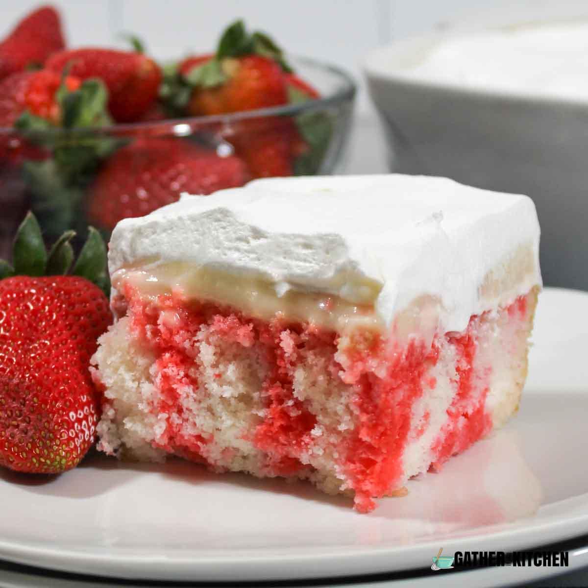Closeup of a piece of Strawberry Jello Poke Cake on a plate.