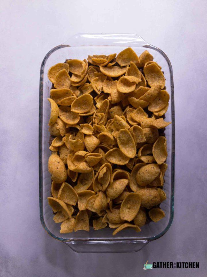 Frito chips layer in casserole dish.