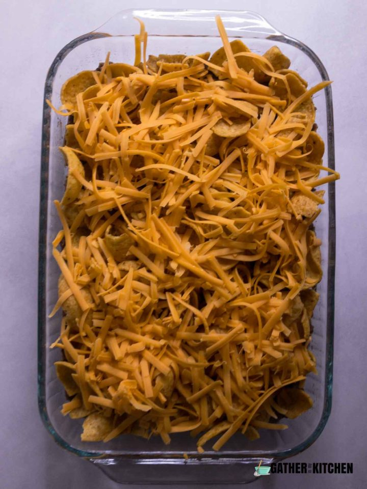 Shredded cheese on top of Frito Chips.