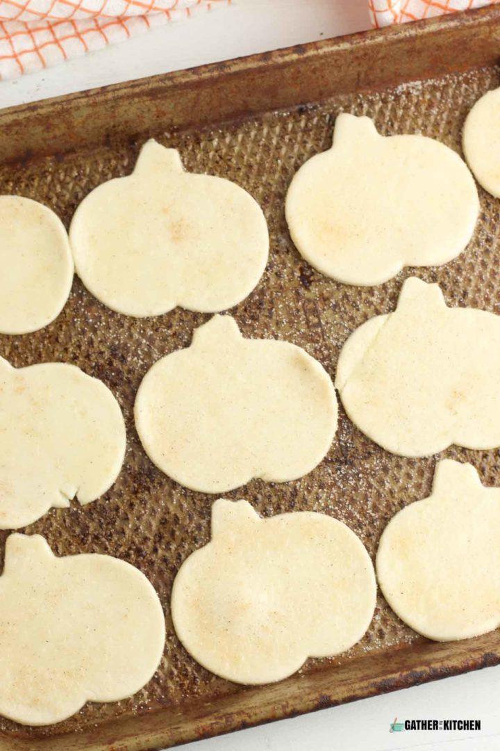 Pumpkin shaped chips on cookie sheet.