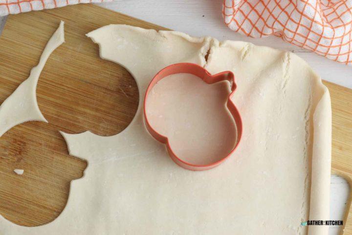 Pumpkin cookie cutter cutting out pie crust.