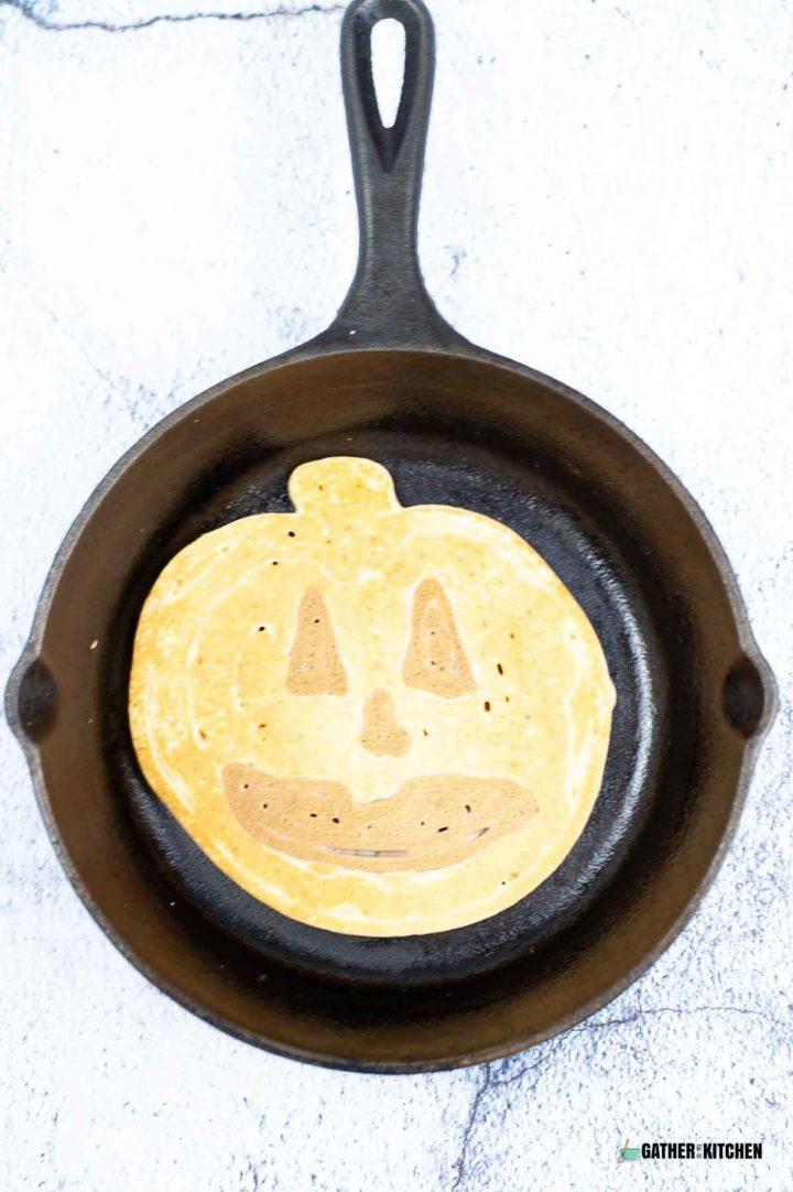 Jack-o-lantern pancake in a skillet.