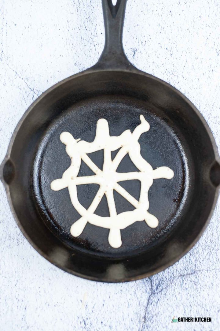 Skillet with pancake batter outlined as spider web.