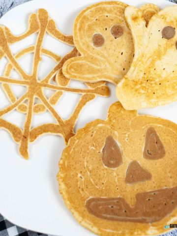 Halloween pancakes in the shapes of a Jack-o-Lantern pumpkin, ghosts, and a spider web on a plate.
