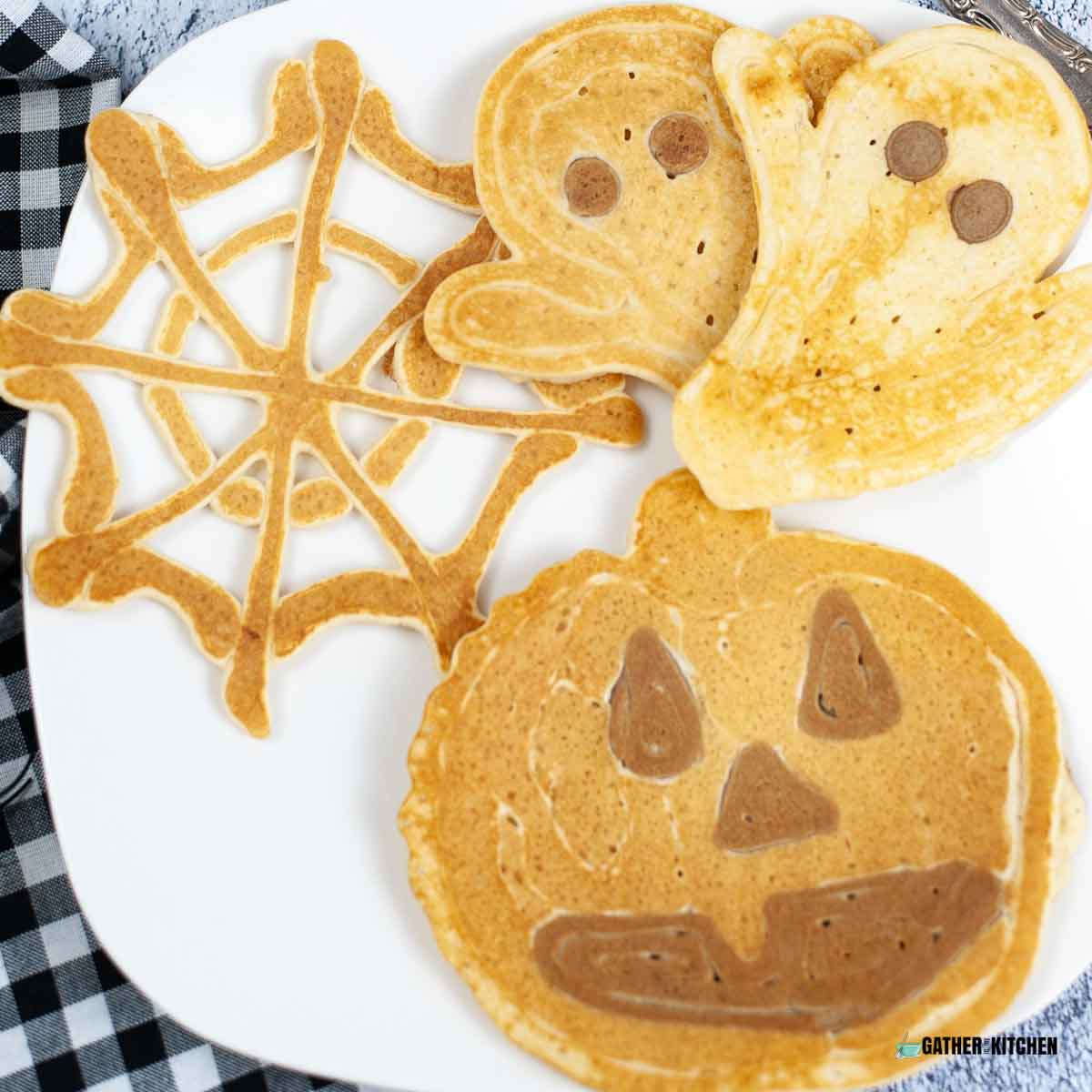 Plate with spider web, ghost, and pumpkin pancakes.