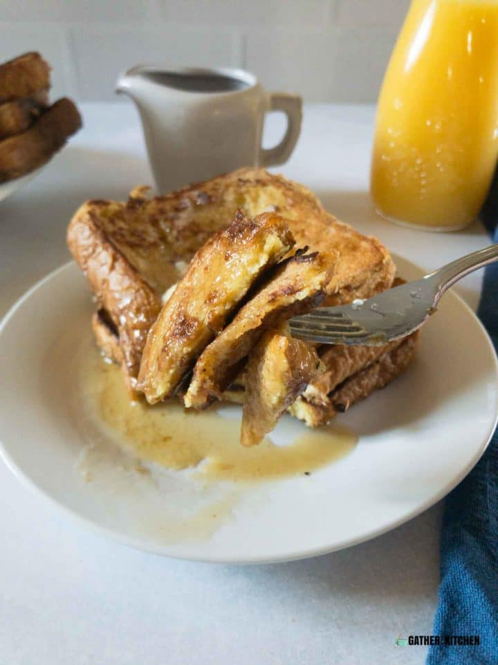 Fork loaded with a bite of French toast.